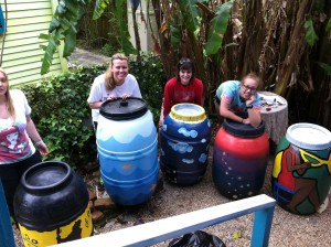 Volunteer artists pose with their beautifully painted rain barrels.